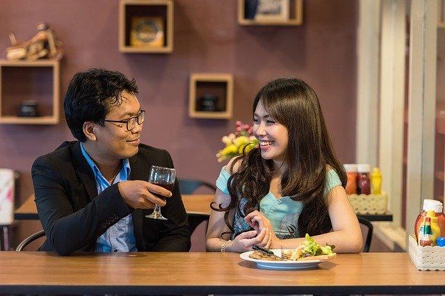 Man en vrouw die lachen en samen eten