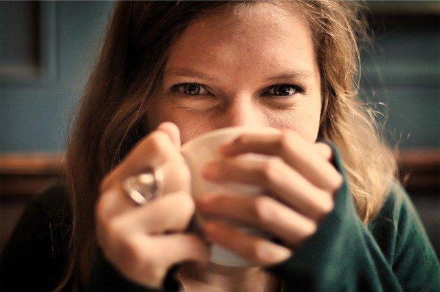 Blije vrouw met een kop thee