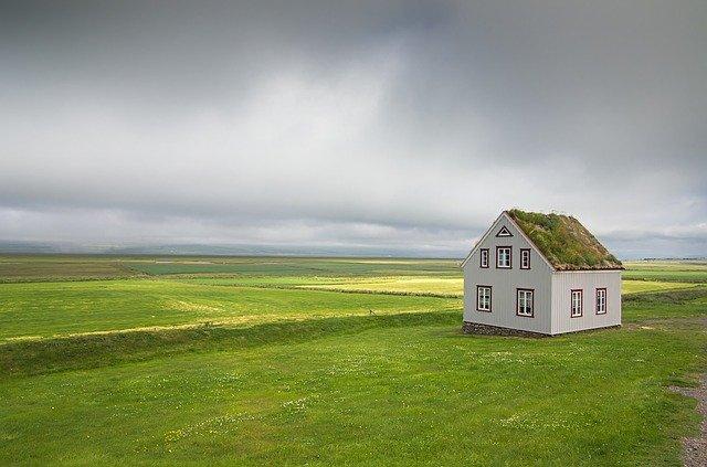 Klein wit huisje met gras op het dak