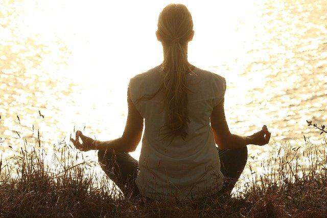 Vrouw die in kleermakerszit mediteert