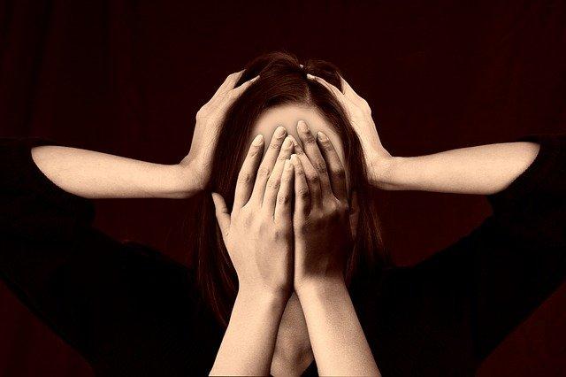 Vrouw in paniek met handen tegen haar oren en ogen