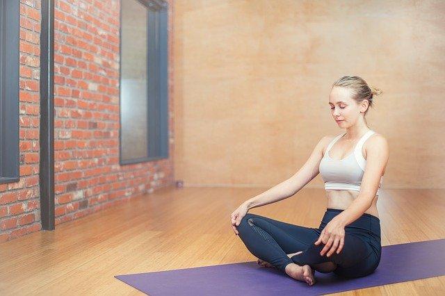 Vrouw in kleermakerszit op yogamat