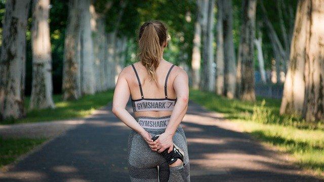 Vrouw met sportkleding die haar spieren opwarmt