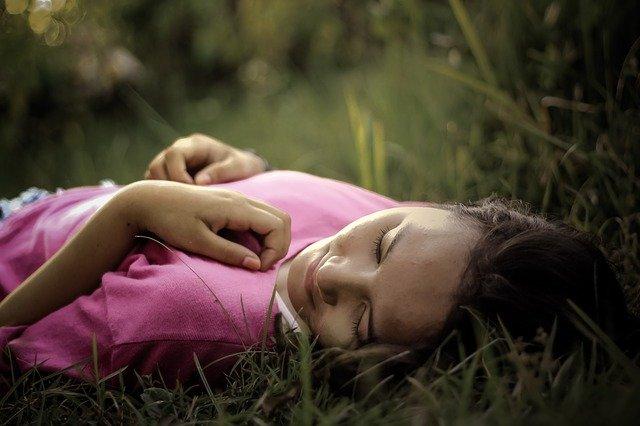 Vrouw die relaxed op het gras ligt