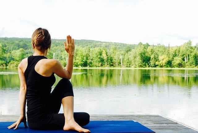 Vrouw in een yogapositie bij het water