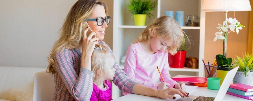 Vrouw die met haar kinderen aan haar werk bezig is.