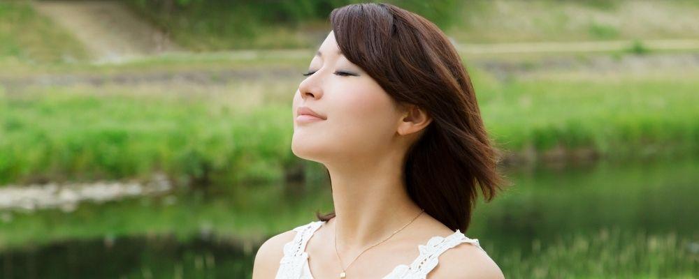 Vrouw die in de buitenlucht diep ademhaalt