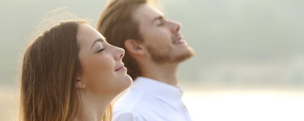 Vrouw en man met gesloten ogen ademen samen diep in