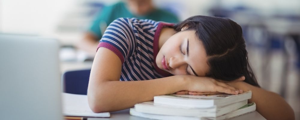 Vrouw slaapt op boeken omdat ze geen energie heeft