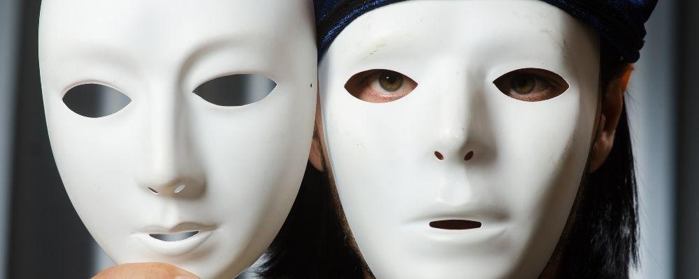 Gemaskerd persoon met een ander masker in de hand