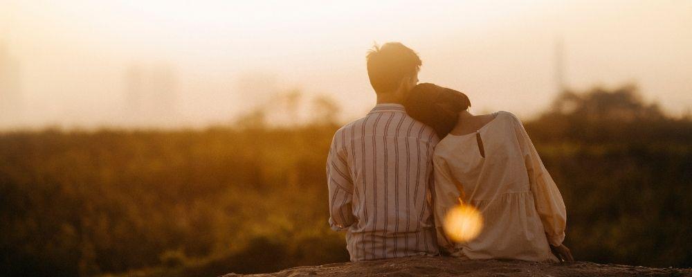 Vrouw leunt tegen man aan en ze kijken samen een veld in