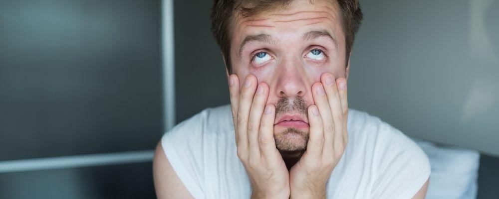 Man die stress heeft en vermoeid is en met zijn handen zijn wangen naar beneden trekt