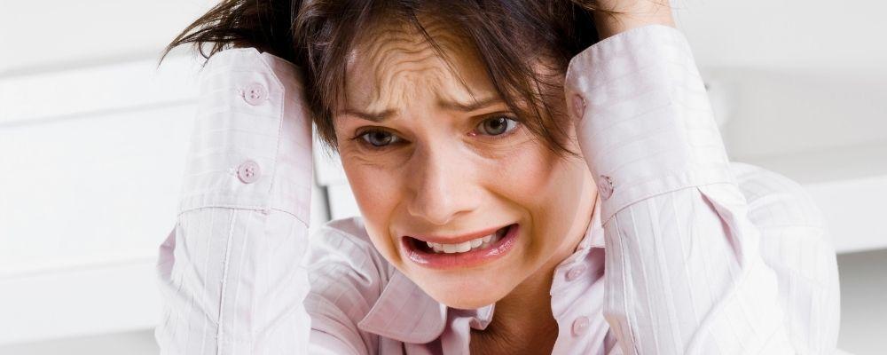 Vrouw met handen in haar haar door stress