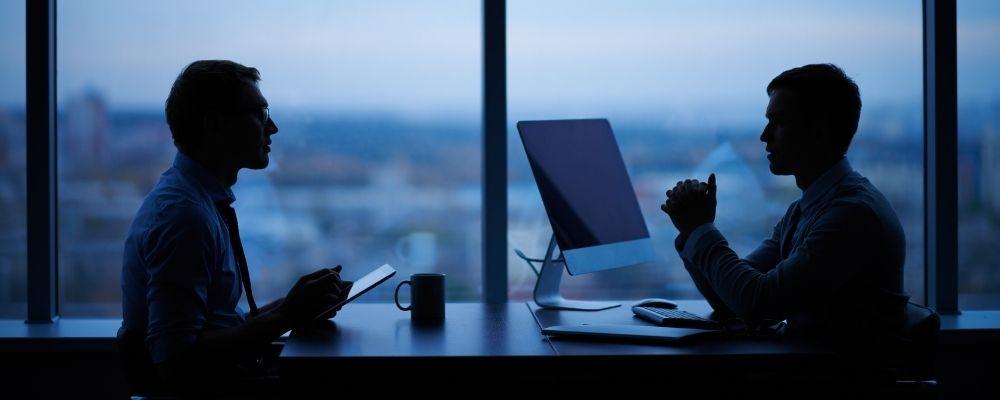 Twee collegas praten samen in een kantoor