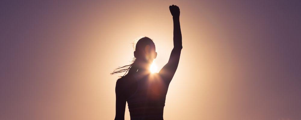 Silhouette van vrouw met vuist omhoog