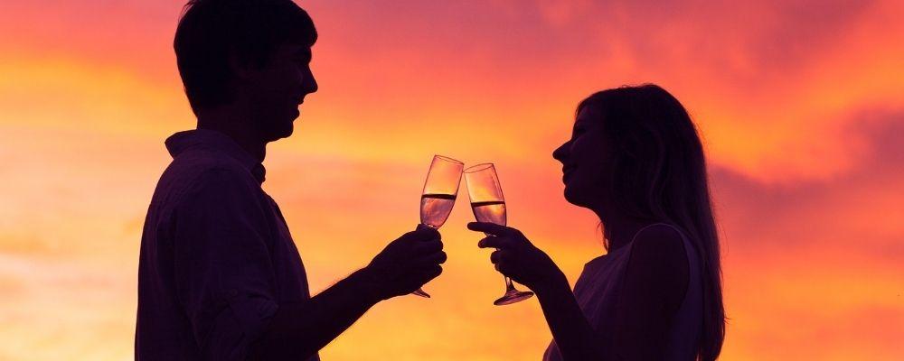 Man en vrouw proosten bij zonsondergang