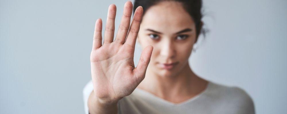 Vrouw houdt hand omhoog als stop teken