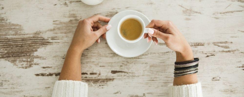 Vrouw heeft een kopje koffie vast en neemt haar tijd