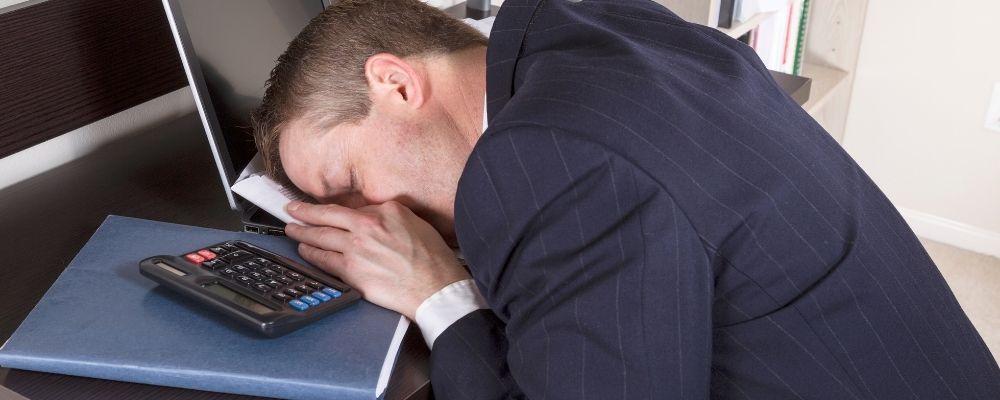 Man ligt op zijn laptop door een burn-out