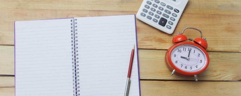 Boekje met een pen, een wekker en een rekenmachine