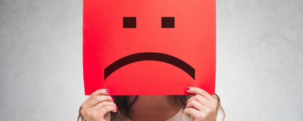 Vrouw houdt een bord met een verdrietig gezicht voor haar hoofd