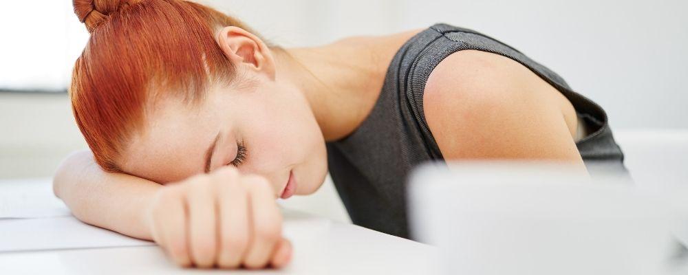 Vrouw ligt op haar arm op tafel door een burn-out