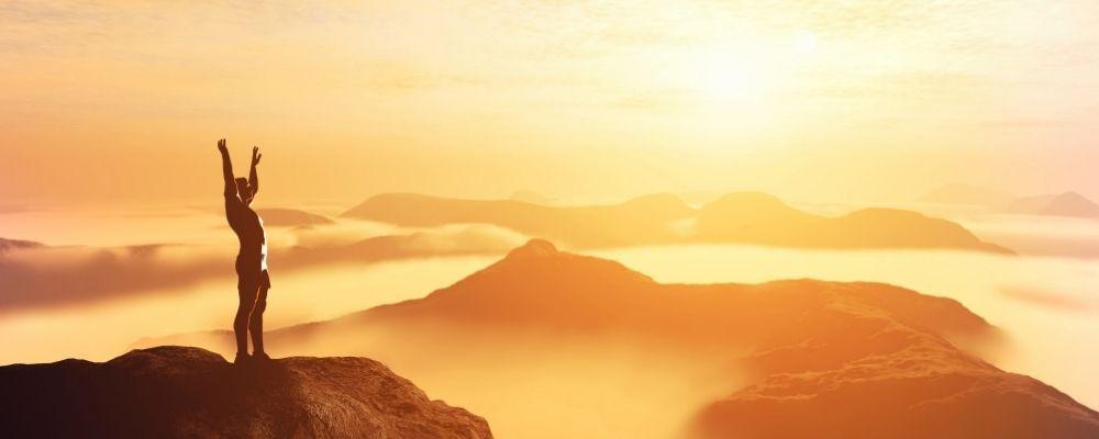 Man met handen omhoog op een berg