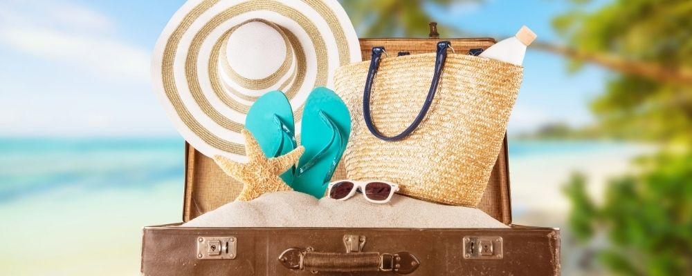 Een koffer met een hoed, slippers en een zonnebril