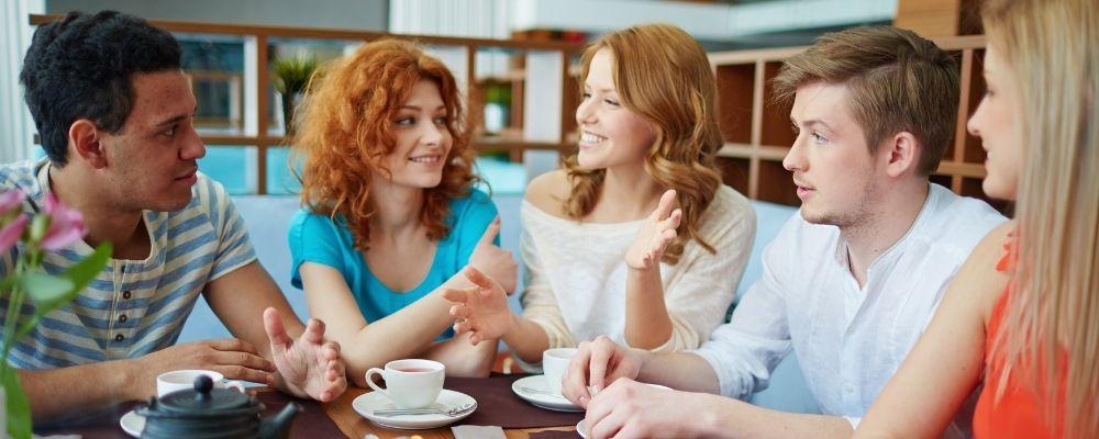 Vrienden die aan een tafel met elkaar praten