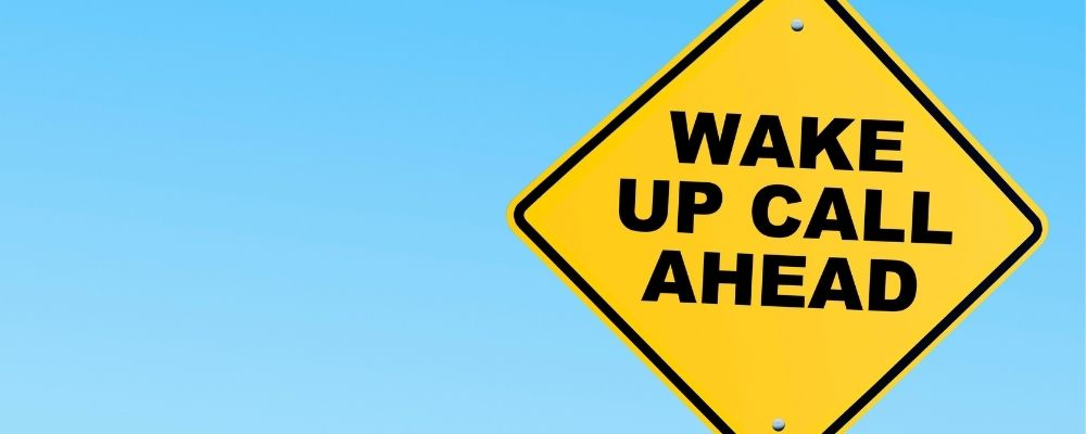Wake up call ahead geschreven op een verkeersbord