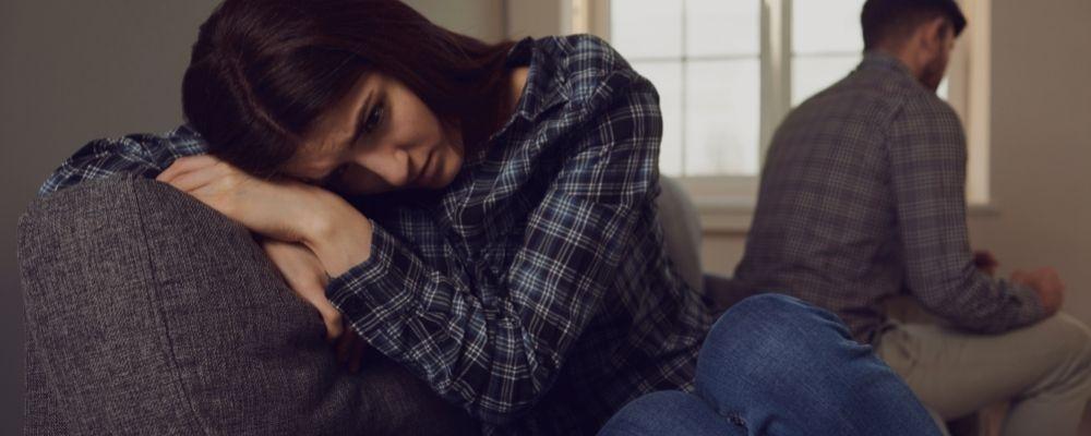 Vrouw zit verdrietig op de bank en wordt genergeerd