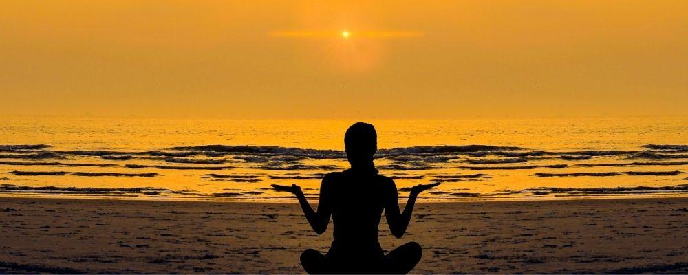 Vrouw doet aan meditatie op het strand bij zonsondergang