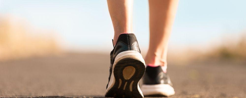 Vrouw met sportschoenen loopt op de weg